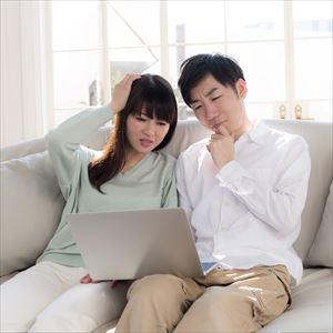 パソコンを見て悩むカップル