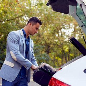 トランクに物を詰める男性