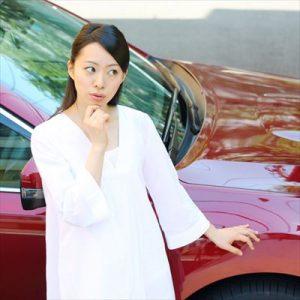 車の前で悩む女性